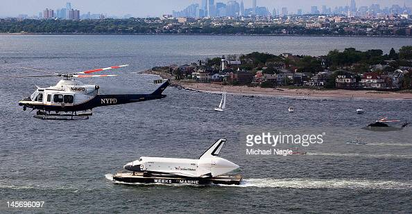 Helicopters fly above Space Shuttle Enterprise as it's carried by barge past Coney Island on June 03 2012 in New York City Enterprise is on it's way...