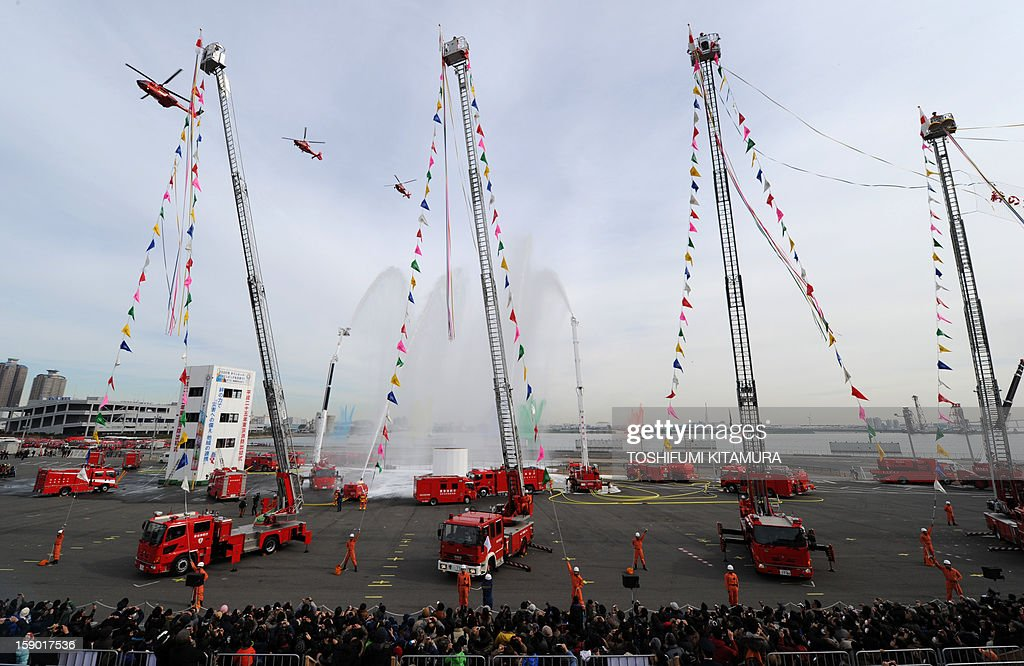 Helicopters fly over a fire engines spray water during the finale of the annual new year fire review in Tokyo on January 6, 2013. A total of 2,800 fire fighters, 133 vehicles, 5 helicopters and 8 boats participated in the new year firefighting exercises. AFP PHOTO / TOSHIFUMI KITAMURA