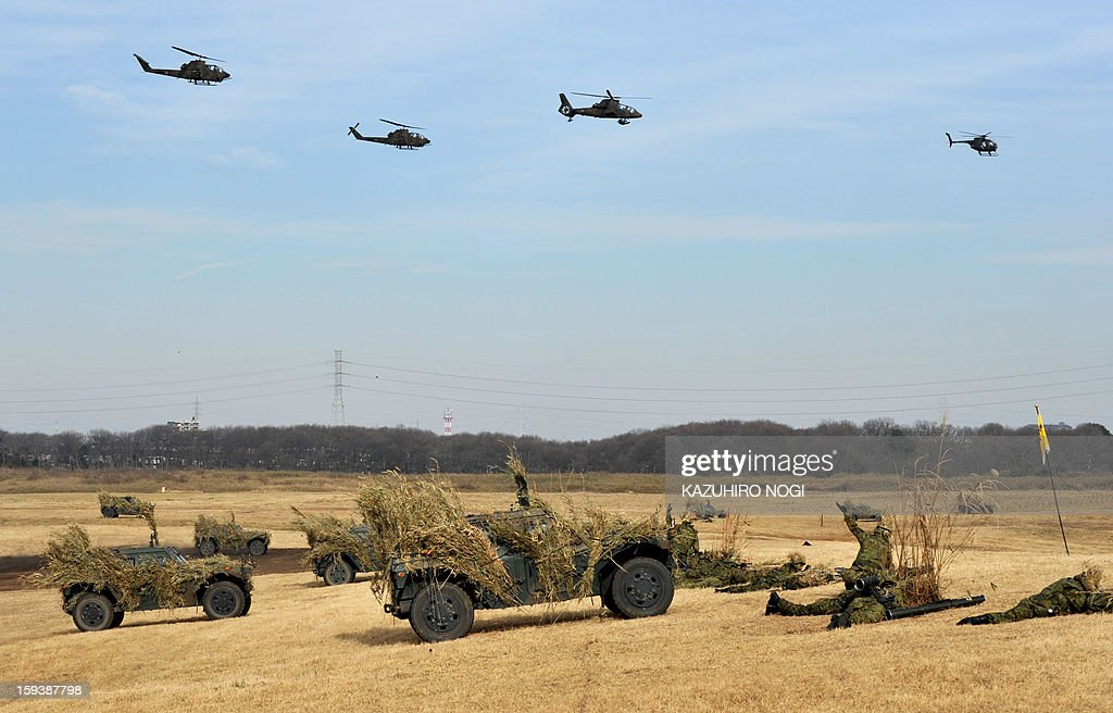 Helicopters fly over Japanese Self Defense Forces ground troops participating in a new year military drill at the training grounds in Narashino, suburban Tokyo on January 13, 2013. A total of 300 personnel, 20 aircraft and 33 vehicles took part in the open exercise at the defense force's Narashino training ground.