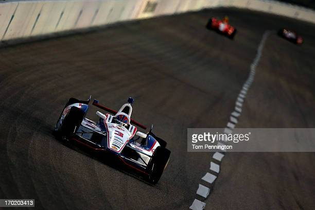 Helio Castroneves of Brazil driver of the AAA Insurance Team Penske Chevrolet leads a group of cars during the IZOD IndyCar Series Firestone 550 at...