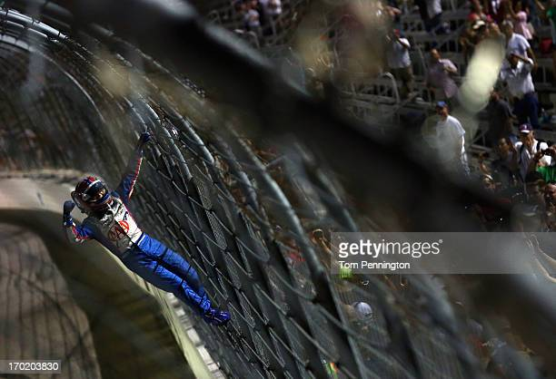 Helio Castroneves of Brazil driver of the AAA Insurance Team Penske Chevrolet celebrates by climbing the fence on the front stretch after winning the...