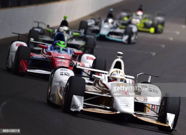 Helio Castroneves of Brazil driver of the Shell Fuel Rewards Team Penske Chevrolet races during the 101st running of the Indianapolis 500 at...