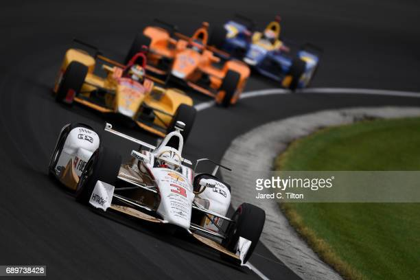 Helio Castroneves of Brazil driver of the Shell Fuel Rewards Team Penske Chevrolet leads a group of cars during the 101st Indianapolis 500 at...