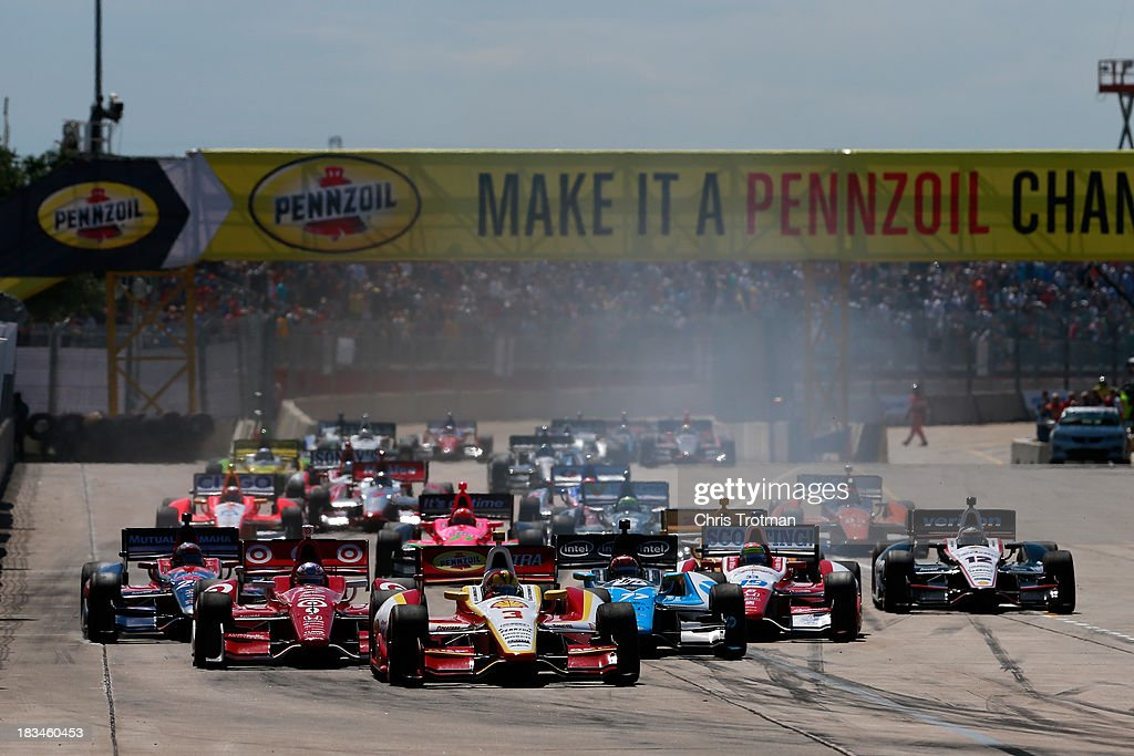 Helio Castroneves of Brazil, driver of the #3 Team Penske Chevrolet Dallara and Scott Dixon of New Zealand, driver of the #9 Target Chip Ganassi Racing Honda Dallara lead a pack of cars at the start of the IZOD IndyCar Series Shell and Pennzoil Grand Prix Of Houston Race #2 at Reliant Park on October 6, 2013 in Houston, Texas.