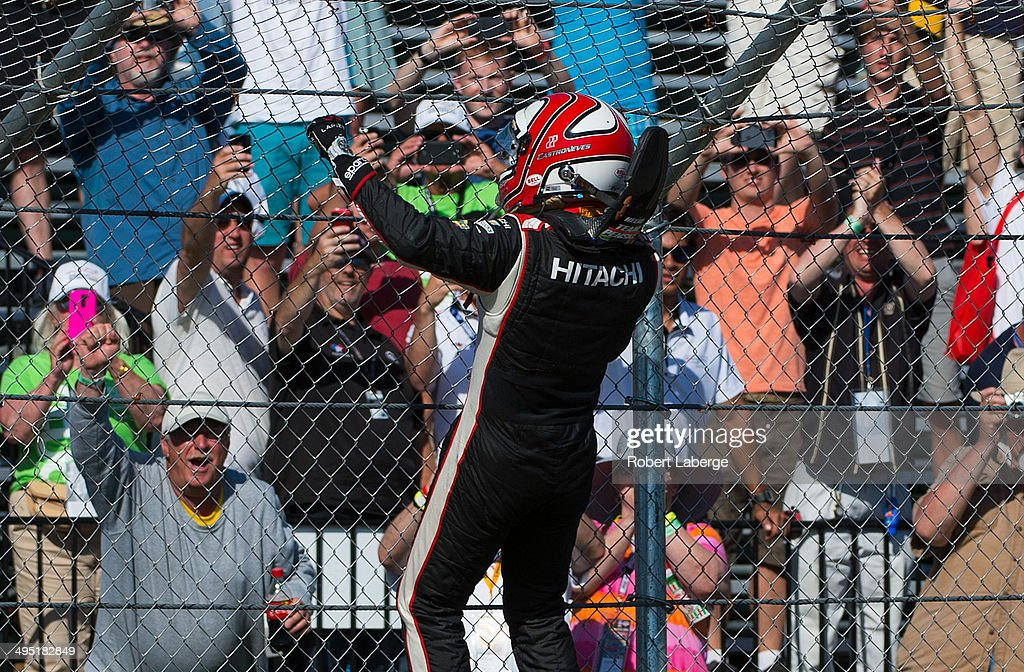 Helio Castroneves of Brazil driver of the #3 Team Penske Dallara Chevrolet celebrates by climbing the fence after winning the Verizon IndyCar Series Chevrolet Indy Dual in Detroit Dual II race at Belle Isle Park on June 1, 2014 in Detroit, Michigan.