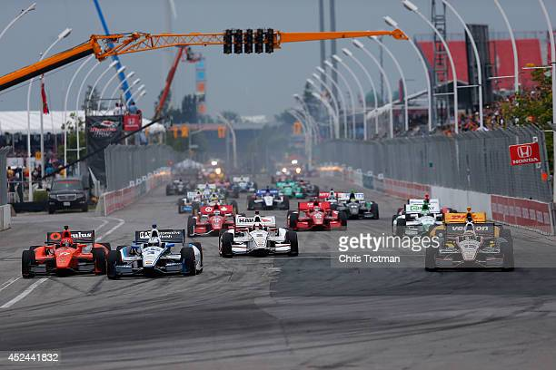Helio Castroneves of Brazil driver of the Team Penske Dallara Chevrolet leads a pack of cars at the start of the Verizon IndyCar Series Honda Indy...