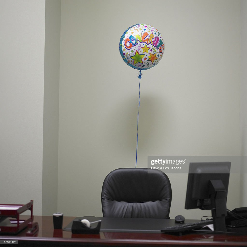 Helium balloon tied to office swivel chair