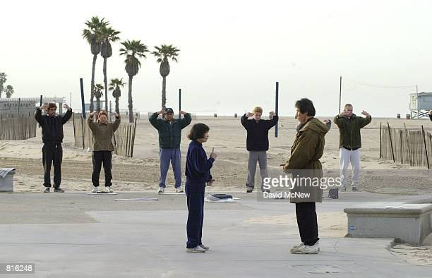 Hellen Lee teaches a man Falun Dafa exercises at Santa Monica State Beach March 3 2001 in Santa Monica CA Also known as Falun Gong Falun Dafa has...
