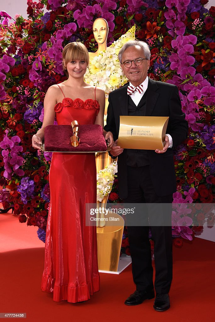 Hellmut Sieglerschmidt and a hostess pose with a Lola Award during the arrivals for the German Film Award 2015 Lola (Deutscher Filmpreis) at Messe Berlin on June 19, 2015 in Berlin, Germany.