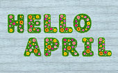 Hello April inscription from the letters of grass with flowers against a background of boards. 3D render.