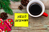 Hello December- handwriting in black ink on a sticky note with a cup of coffee and mittens, New Year resolutions concept.