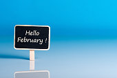 Hello February words on little wooden tag at blue background with empty space for text, template or mockup.