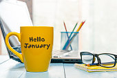 Hello January written on yellow coffee cup at manager or freelancer workplace. New year time concept. Business and office background.
