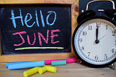 Hello June. Back to school concept. Alarm clock on wooden with blackboard on background