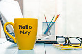 Hello MAY - text on yellow coffee cup at business office background, workplace with laptop and glasses. Spring time, empty space for text.