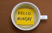 hello Monday written on a sticky note placed in an empty coffee cup.