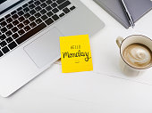 Hello Monday text with smiley face on sticky note on desk