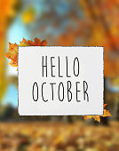 Hello October autumn text on white plate board banner fall leaves blur background