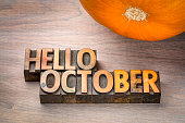 hello October greeting card - letterpress wood type blocks against grained wood with a pumpkin