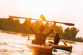 Rear view of beautiful young couple kayaking on lake together and raising up their paddles