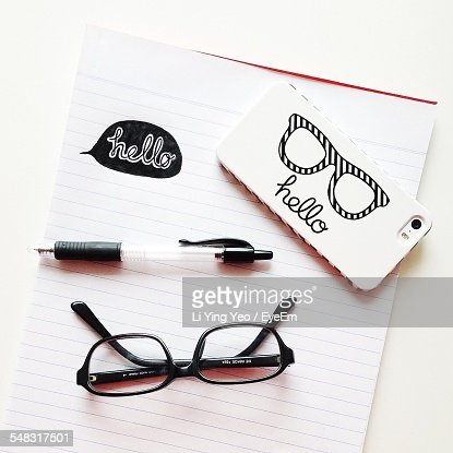 Hello Text Printed Mobile Phone On Notepad With Eyeglasses And Pen
