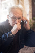 Sick senior man using phone.