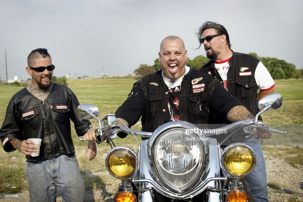 Hells Angels motorcycle club member Monster (C) shows off his Indian motorcycle to club members Big Lou (L) and Bone during a Hells Angels rally July 26, 2003 in Peru, Illinois. The Hells Angels hosted a rally and bike show in the central Illinois town.