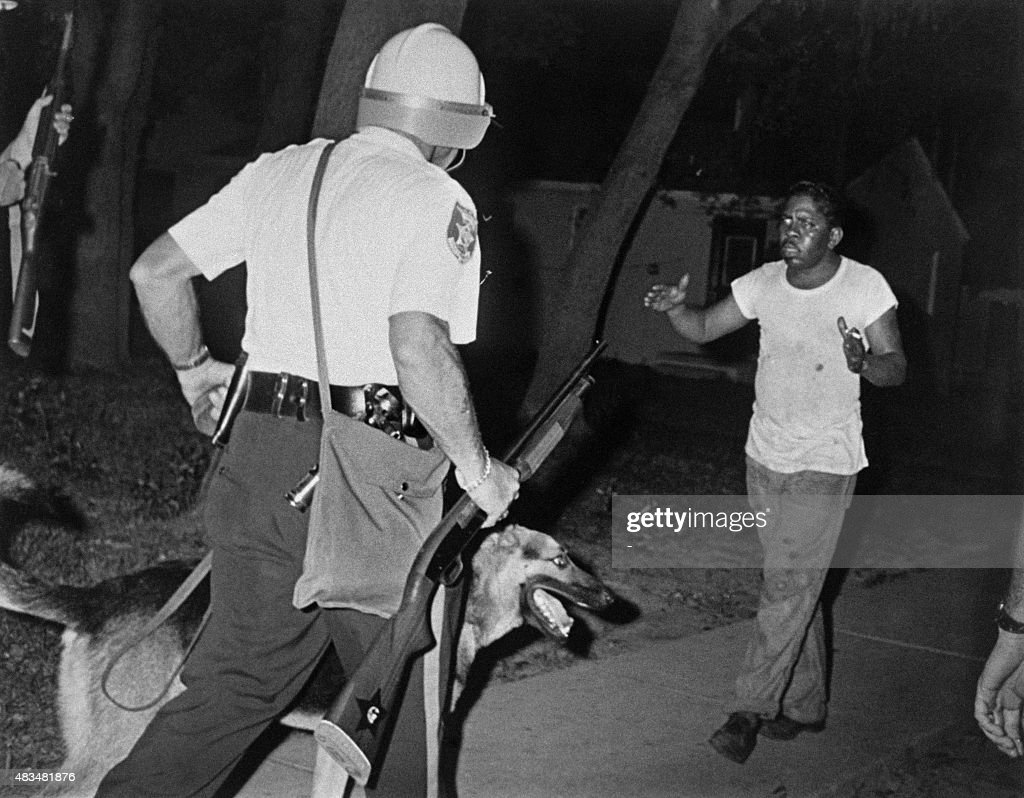 Helmeted police riot argue with an African american man as Newark witnessed its second night of rioting on July 14, 1967. / AFP / -
