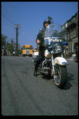 Helmeted policeman on motorcycle escorting students to newly integrated high school in South Boston during crisis precipitated by busing law