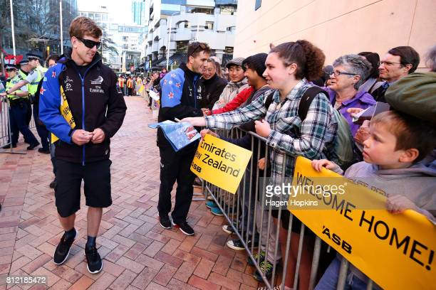 Helmsman Peter Burling and cyclist/foil trimmer Blair Tuke sign autographs during the Team New Zealand Americas Cup Wellington Welcome Home Parade on...