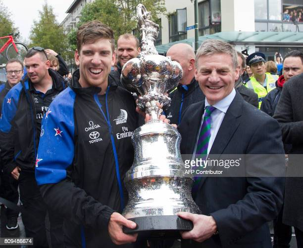 Helmsman Peter Burling and New Zealand Prime Minister Bill English pose with the America's Cup yachting trophy as members of the Emirates Team New...