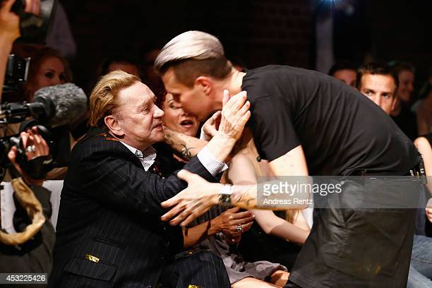 Helmut Berger shakes hands with designer Florian Wess after the GarconF fashion show at BalloniHallen on August 5 2014 in Cologne Germany