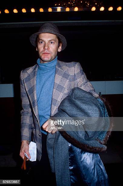 Helmut Berger wearing a plaid jacket carrying a fur timed overcoat circa 1970 New York