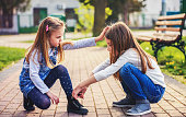 Love and care for younger sister. Little girl tying shoes of her sister