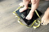 Help fat or obese child with toddler on weight scale, supervised by a parent