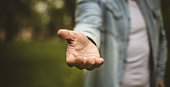 Help is always welcome. Young man in standing in park stretches his hand. Focus is on hand. Close up.