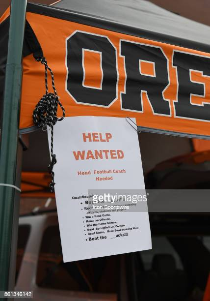 A help wanted sign hangs from a fan's canopy advertising the need for a new head coach during a college football game between the Colorado Buffaloes...