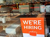 A Help Wanted sign on the front window of a kitchen store in California