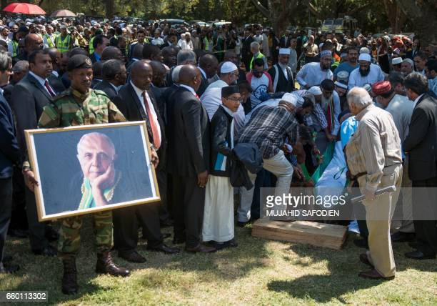 TOPSHOT Helpers put the body of late South African antiapartheid activist Ahmed Kathrada into the grave as South African ruling party African...