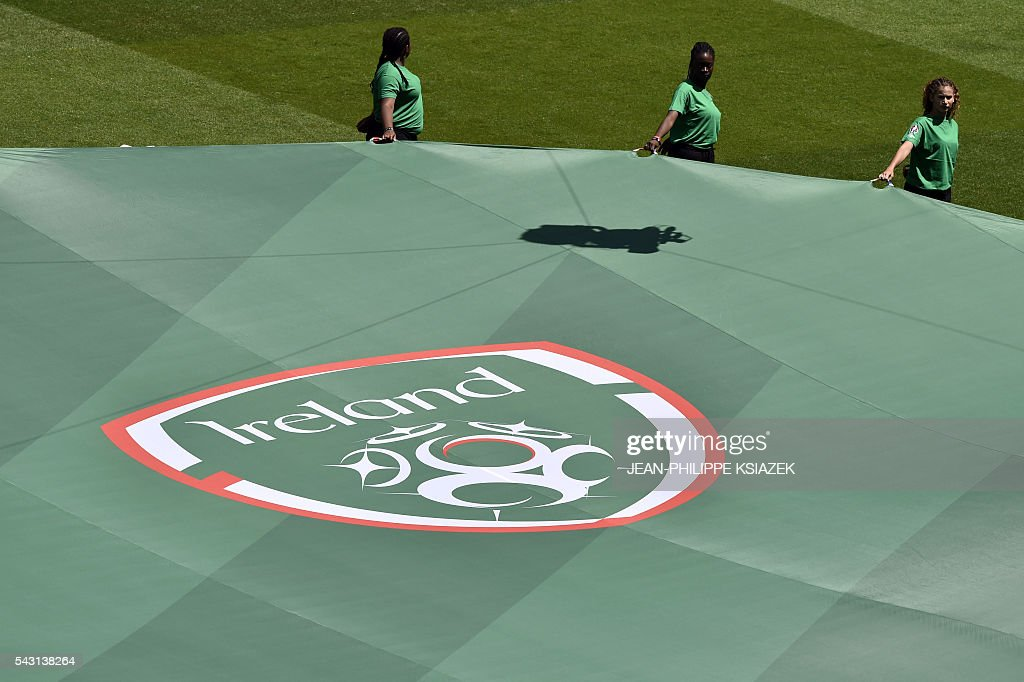 Helpers stand with a large banner with the logo of the Irish Football Federation (IFA) during the opening ceremony ahead the Euro 2016 round of 16 football match between France and Republic of Ireland at the Parc Olympique Lyonnais stadium in Décines-Charpieu, near Lyon, on June 26, 2016. / AFP / JEAN