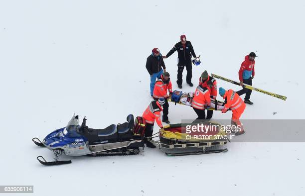 Helpers transport Austria's ski jumper Gregor Schlierenzauer after a crash during his qualification jump for a second FIS ski jumping World Cup...