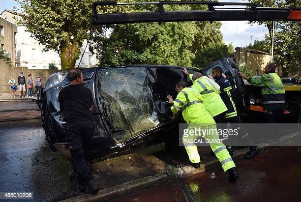 Helpers turn a damaged Ford Fiesta car in which two people died after the car was swept away by waters to be loaded onto a truck in Montpellier on...