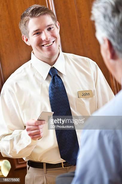 Serviable Travailleur donner la clé de la chambre pour les hôtes