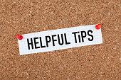 Helpful tips note paper pinned on cork bulletin board.