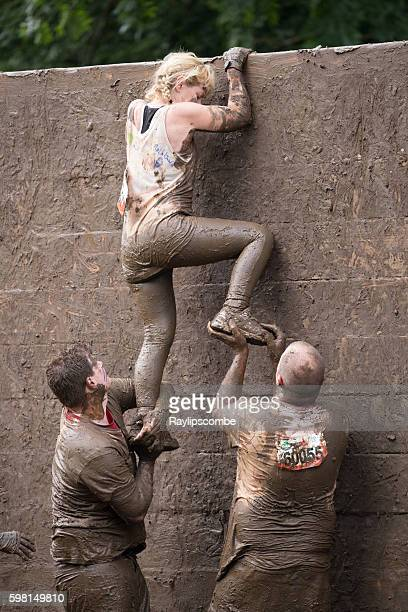 Helping hand for a woman climbing a slippery wall