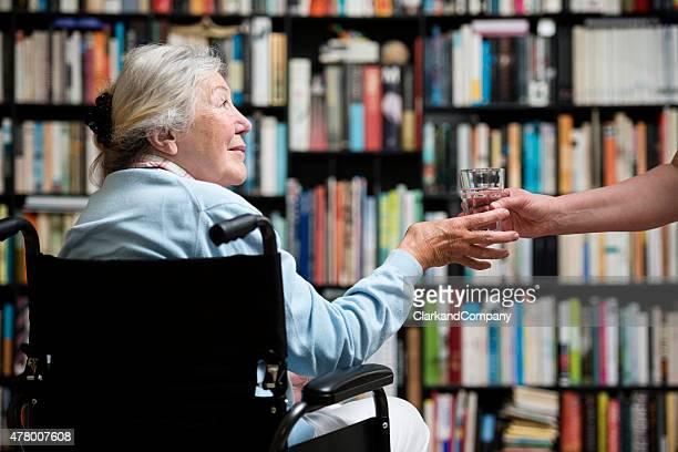 Aider la main pour fauteuil roulant; Femme âgée obtenir de l'aide.