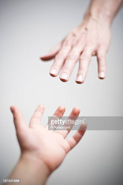 Helping hands, reaching out for help, shallow focus on fingertips