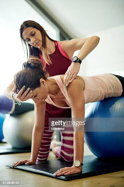 Helping her get the most out of her pilates workout