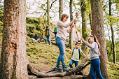 Young family have discovered a rope swing while out on a hike together. The children are helping their mum to get on the swing.