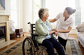 Shot of a smiling caregiver helping a senior woman in a wheelchair at home